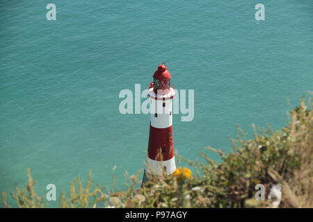 Beachy Head, UK - July 14 2018: Beachy Head Lighthouse seen fron the chalk cliff  on a hot summers day on 14 July 2018. Temperatures raised to 27 degrees and is expected to stay high for another month. The cliff, the highest chalk sea cliff in Britain rises to 162 metres above sea level and unfortunately one of the most notorious suicide spots in the world. Credit: David Mbiyu - Stock Image