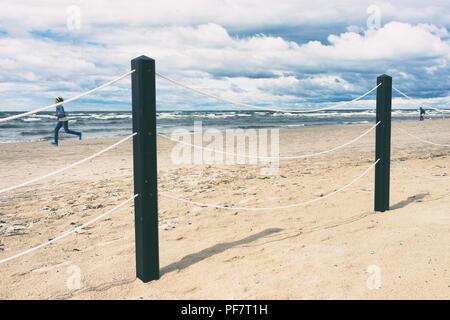 The girl runs along the beach on the Baltic Sea - Stock Image