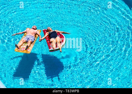 Total relax for happy mature senior retired people lay down on coloured lilos inflatable mattress on blue clear water of swimming pool in summer time  - Stock Image