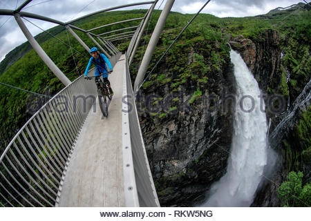 Man rides a mountain bike across the Gorsa Bridge over the Gorza canyon and Gorzi Waterfall in Lyngenfjord in Norway during the summer months. - Stock Image