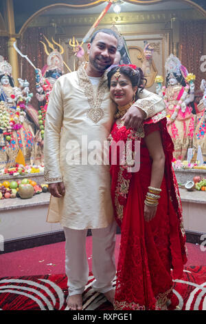 Posed portrait of a Hindu couple just prior to their wedding ceremony at a temple in Ozone Park, Queens, New York City. - Stock Image