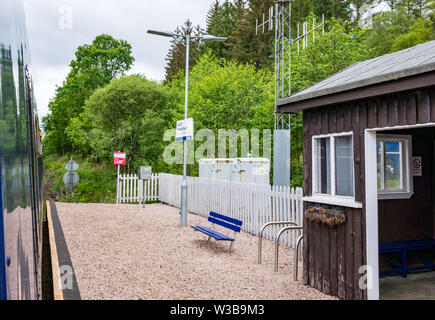 Loch Eil rural train station platform and name sign with ScotRail train on West Highland railway line, Scottish Highlands, Scotland, UK - Stock Image