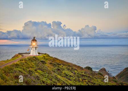 Cape Reinga Lighthouse, Northland, New Zealand, with its light on at twilight. - Stock Image