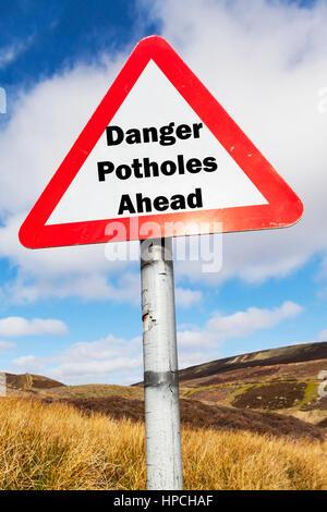 Danger potholes ahead sign UK roads danger dangerous because of potholes everywhere - Stock Image