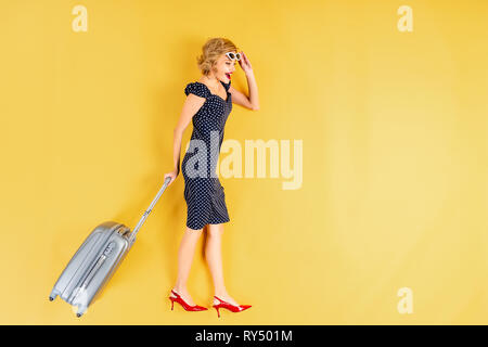 Charming young woman in dress and high-heeled shoes holding suitcase on yellow background - Stock Image