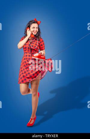 happy young pinup standing woman in red dress and nylon stockings talking  on phone over blue background - Stock Image