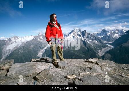 A climber poses on the summit of Aiguille de la Belvedere in the Chamonix Alps, France - Stock Image