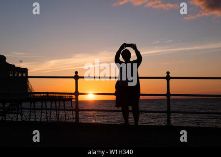 Aberystwyth Wales UK, Tuesday 02 July 2019  UK Weather: A woman takes a selfie, silhouetted against the sky as they watch the glorious sunset in Aberystwyth on the Cardigan Bay coast, west Wales.   photo credit: Keith Morris//Alamy Live News - Stock Image