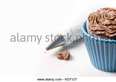 Chocolate cup cake with ganache chocolate cream and piping bag in the background on the white marble background. - Stock Image