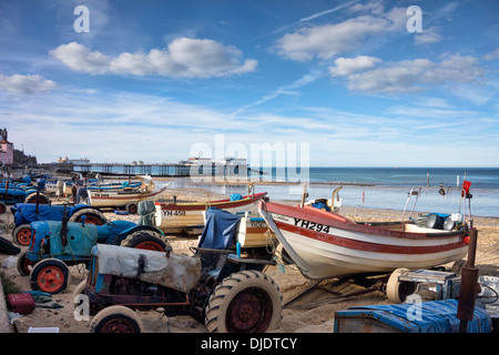 Old tractors get a second career as fishing boat launchers on Cromer Beach, Norfolk, England - Stock Image