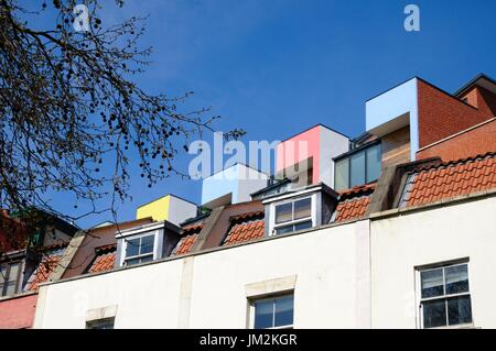 Abstract view of rooftops of Victorian or Edwardian terraced houses juxtaposed with modern terraced housing rising above from behind - Stock Image