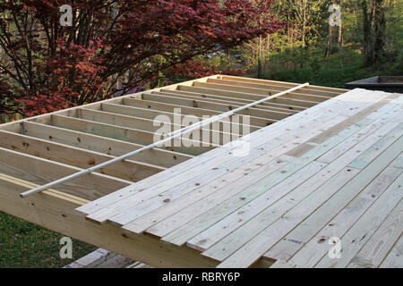 The ongoing construction of an elevated outdoor wooden deck on a late afternoon in Springtime - Stock Image