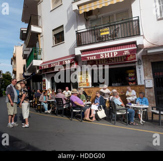 British holiday makers and ex pats enjoy a drink in the November sun in Torremolinos, Cota del Sol, Andalucia, Spain. - Stock Image