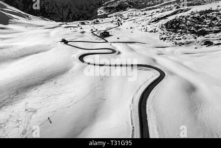 View of a winding road in the snow in Passo Giau, high alpine pass near Cortina d'Ampezzo, Dolomites, Italy - Stock Image