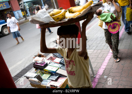 A Filipino boy carries a load of fresh bananas in Manila, Philippines. - Stock Image