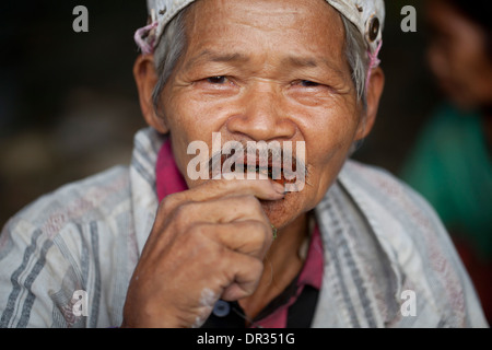 A Hanunoo Mangyan man placing fresh batch of betel chew, or nga nga, in his mouth in Oriental Mindoro, Philippines. - Stock Image