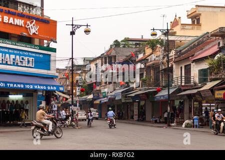 Typical street view of a road and the buildings and shops with people on mopeds, Hanoi, Vietnam - Stock Image