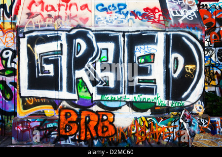 wall of graffiti with greed in large letters - Stock Image