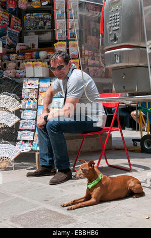 Kiosk keeper selling postcards and dog in Calle Canonica Venice Italy - Stock Image