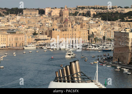 Exhaust from the smokestack of a cruise ship clearly visible against the background of Birgu in Malta. Carbon emissions from ships and global warming. - Stock Image