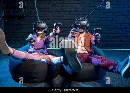 Man and woman shooting with gamepads while playing in virtual reality using VR headsets in the playing room - Stock Image