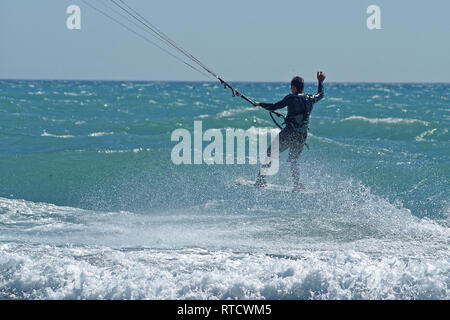 Kite boarder  flying over the waves during a windy day in french riviera - Stock Image