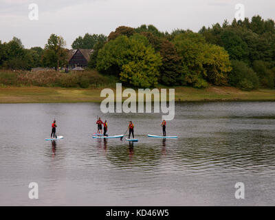 People learning to stand up paddle board on Tittesworth Water reservoir, The Peak District, Staffordshire, UK - Stock Image