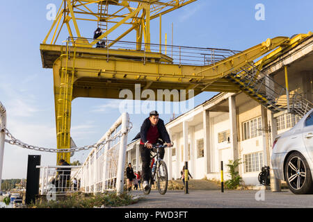 Man cycling along the bicycle path on the Sava River waterfront passing the yellow crane of the Belgrade Port. - Stock Image