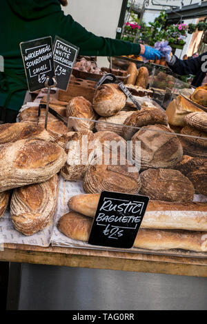 Rustic authentic Baguette and Sourdough breads at Borough Market Bakery. Speciality bread Borough Market Bakery 'Bread Ahead' stall inside with variety of attractive hand made artisan breads on display for sale. Artisan speciality bakery stall at Borough Market Southwark London UK - Stock Image
