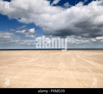 Blowing sand in High wind on wide St Andrews West Sands beach with blue sky and white clouds and North Sea at St Andrews Fife Scotland UK - Stock Image