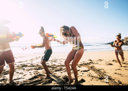 People having fun together in friendship at the beach playing with water guns in bikini under the hot summer sun - craziness and friends - bright imag - Stock Image