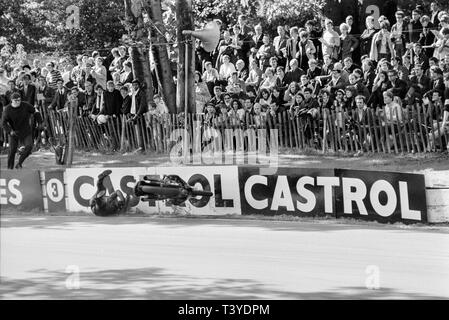 Motorcycle racing at Crystal Palace near London in 1968. A motorcycle racer crashes and falls in to the circuit wall whilst approaching in to a bend on the track. The Crystal Palace racing circuit was closed in 1972. - Stock Image