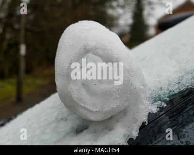 Ashbourne, Derbyshire. 2nd Apr, 2018. UK Weather: snow scrolls on a car windscreen 1' of morning snow quickly melts causing flooding on Easter Bank Holiday Monday in Ashbourne, Derbyshire Credit: Doug Blane/Alamy Live News - Stock Image