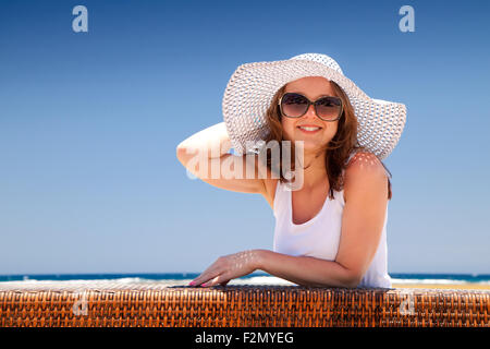 The young beautiful woman in a hat on holidays, on a sunny beach - Stock Image