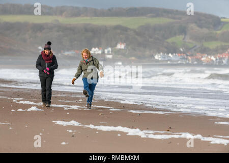 Two females walking the North Yorkshire coast from Sandsend too Whitby. - Stock Image