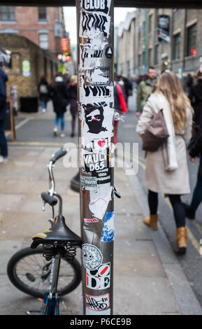 Street view of sign post in trendy Brick Lane decorated with a variety of artistic stickers and with a BMX leaning against it. London, England. - Stock Image