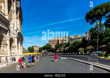 Rome, Italy - 24 June 2018: People at the entrance of the Roman Forum and the Great Roman Colosseum (Coliseum, Colosseo), also known as the Flavian Am - Stock Image