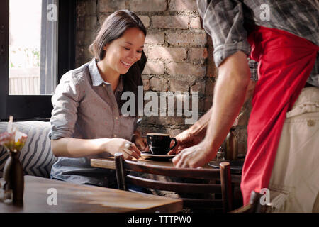 Midsection of owner serving coffee to customer in cafe - Stock Image
