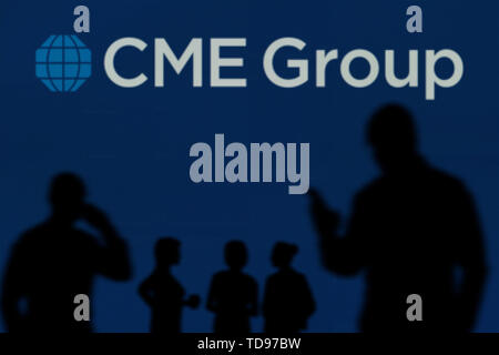 The CME Group logo is seen on an LED screen in the background while a silhouetted person uses a smartphone in the foreground (Editorial use only) - Stock Image