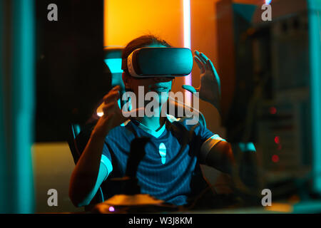 Positive young male gamer in tshirt sitting at table and using virtual reality simulator while playing video game - Stock Image