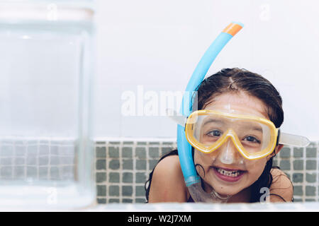 portrait of a happy pretty little girl smiling and having fun with snorkel goggles in the tub while taking a bath in the bathtub, kids hygiene concept - Stock Image