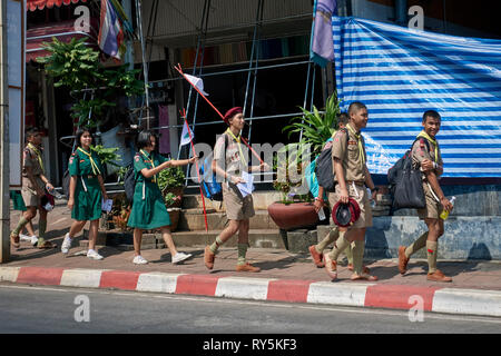 Scout group. Thailand mixed group of boy scouts and girl guides walking along the street to a recreational camp site. Thailand Southeast Asia - Stock Image