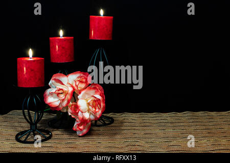 Beautiful orange and white roses, red candle perched on black candle holders on mesh place mat and wooden table with dark background. Valentines, Moth - Stock Image