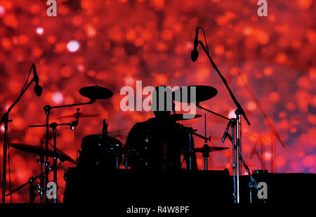 A silhouette of a drummer in a music concert against a red pattern screen behind. - Stock Image