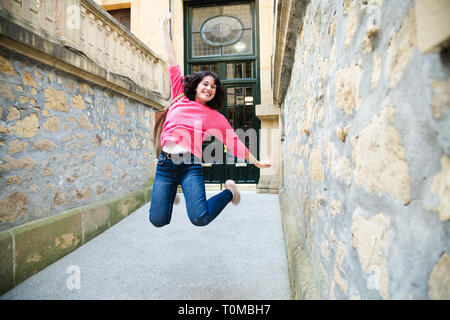 Happy young woman in pink sweater jumping when leaving home. Some blur beacuse of the movement - Stock Image
