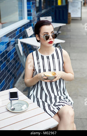 Woman in striped minidress outside a cafe looking away - Stock Image