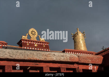 Dharmachakra flanked by two deers and Dhvaja the victory banner in golden metalic form on the roof of Jokhang temple. - Stock Image