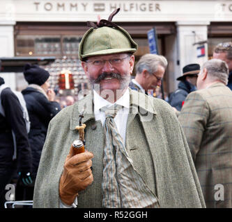 A smiling man in period costume poses near his vehicle, in the Veteran Car Zone of the 2018 Regents Street Motor Show - Stock Image