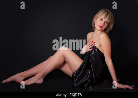 Young woman sitting on a black background - Stock Image