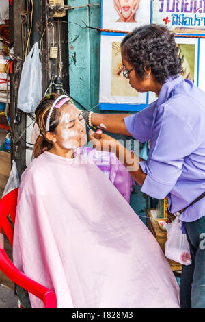 Bangkok, Thailand - April 21st 2011: Woman threading a womans face on the street. This occurs in a particular part of Chinatown - Stock Image